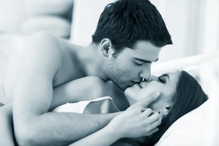 couple au lit: Jeune couple passionné de faire l'amour au lit Banque d'images