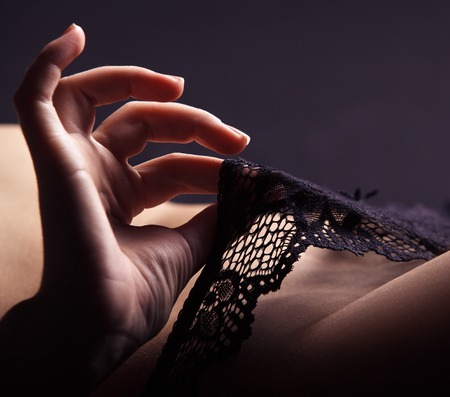 nude women: Playful hand touching black panties Stock Photo