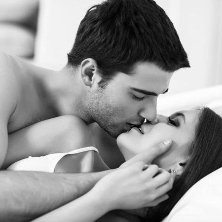침대에서 사랑을 나누는 젊은 열정 부부 스톡 콘텐츠