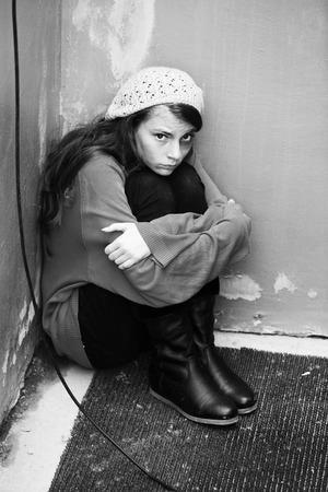 Homeless girl sitting on the floor