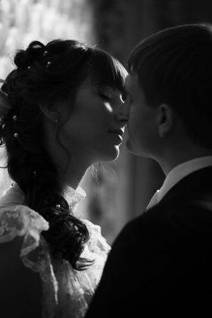 dim light: Newlyweds kissing. Dim light. Close up image