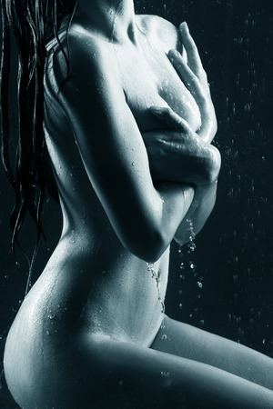 nude wet: Young sexy woman sit on the floor. Water studio photo.