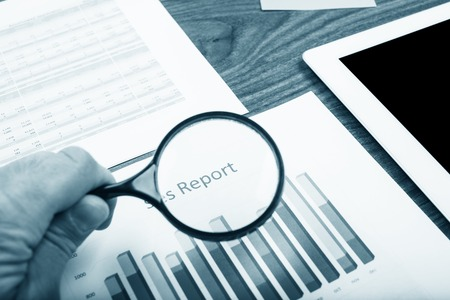 Businessman checking a graph with a magnifying glass, closeup photo