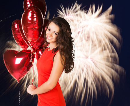 Sexy happy woman with balloons over fireworks background photo