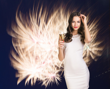Sexy happy woman with champagne glass over fireworks background photo