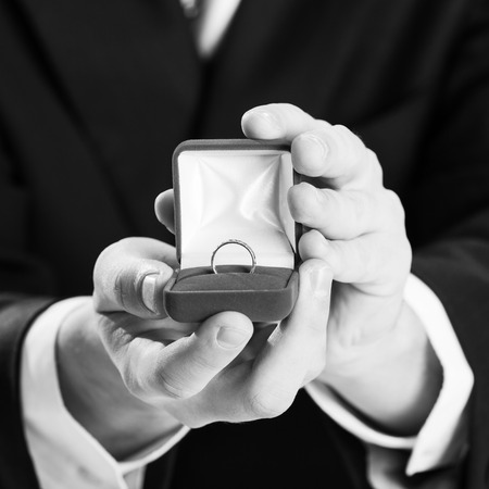 Close up of man holding wedding ring and gift box. photo