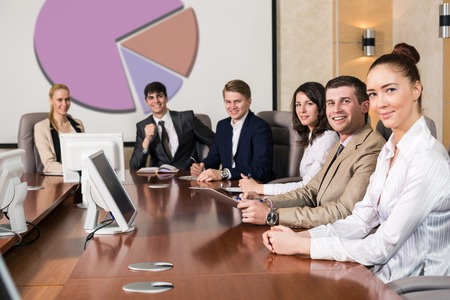 Businesspeople Sitting At Conference Table At The Meeting photo