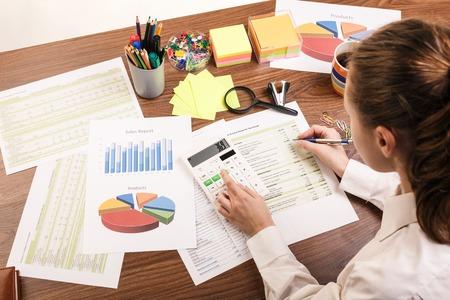Primo piano di un calcolatore mano femminile, sulla scrivania dell'ufficio.