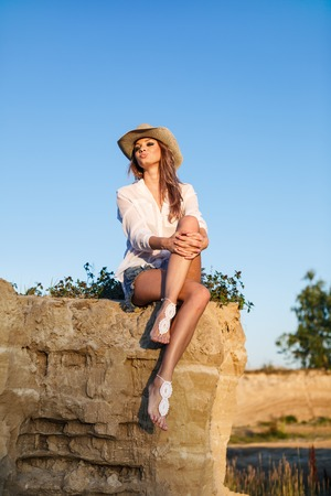 area sexy: On the edge. Beautiful woman sitting on the edge of a precipice Stock Photo