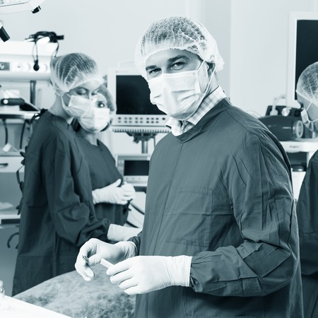 Surgeon looking at camera with colleagues photo