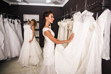 Two young beautiful brides trying her dress in shop