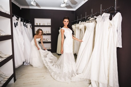 wedding dress: Smiling pretty bride chooses white gown at shop of wedding fashion