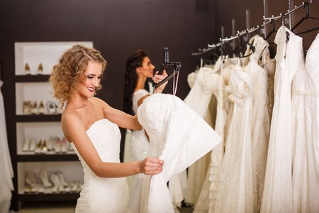 wedding dress: Two young beautiful brides trying her dress in shop