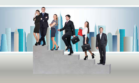 Young businesspeople standing on stairs over a city background photo