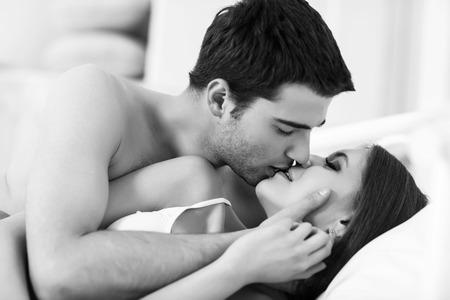 young couple sex: Молодая страстная пара заниматься любовью в постели Фото со стока