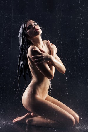 junge nackte mädchen: Junge reizvolle Frau auf dem Boden sitzen. Wasser Studio Foto. Lizenzfreie Bilder