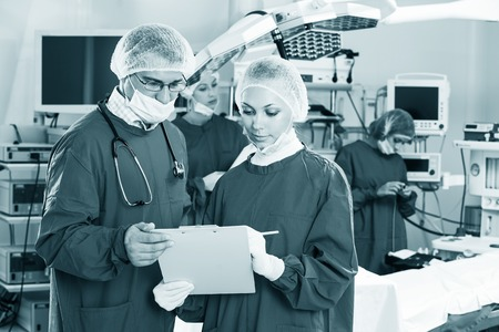 Portrait of surgeons in surgery with doctors working on background photo