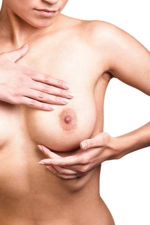 Young woman examining her breasts for signs of breast cancer isolated on white background photo