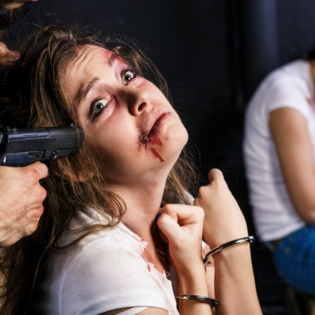 abducted: Crime. Two beautiful girls in the Business clothing kidnapped by criminals. Terrorist is threatening hostages with a gun. Stock Photo