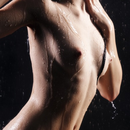 wet breast: Taking shower. Female Curves in front of black background