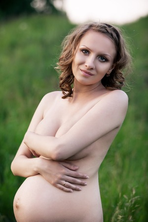 Portrait of 6 months nude pregnant woman on nature