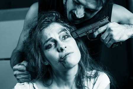 Crime. Beautiful girl kidnapped by criminals. Terrorist is threatening hostages with a gun.