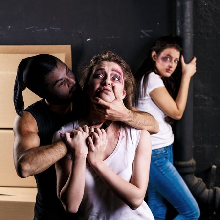 abducted: Crime. Two beautiful girls kidnapped by criminals. Terrorist is threatening hostages with a knife Stock Photo