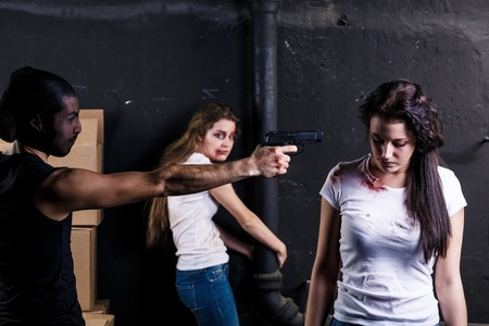Crime. Two beautiful girls kidnapped by criminals. Terrorist is threatening hostages with a gun. Stock Photo