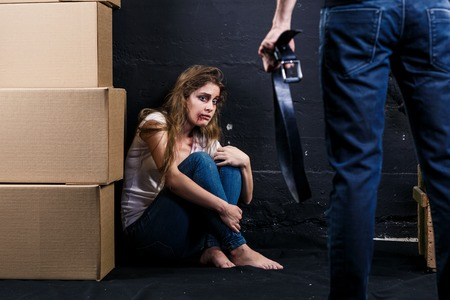 Young woman is a victim of domestic violence and abuse siting on the floor is scared of man with belt. Stock Photo