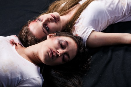 Two young beaten women with cuts and bruises lie down on the floor on black background Stock Photo