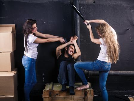 Zwei junge Frauen geschlagen Mann sitzt auf dem Kasten im Keller