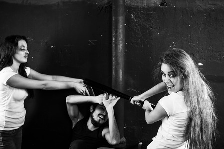 Two young women beating and shooting man on black-and-white background photo