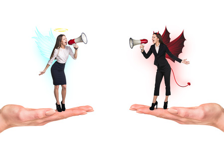 Portrait of angel and devil girls with megaphone standing on palms and copyspace between them on white background