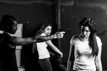 hostages: Crime. Two beautiful girls kidnapped by criminals. Terrorist is threatening hostages with a gun. Stock Photo