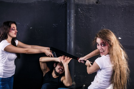 Two young women beating and shooting man photo