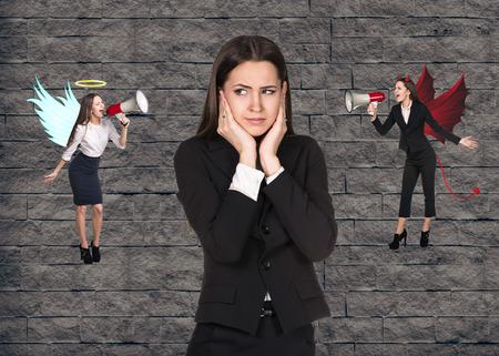 conflicto: Opci�n de fabricaci�n empresaria joven con problemas entre el bien y el mal en el fondo de ladrillo gris
