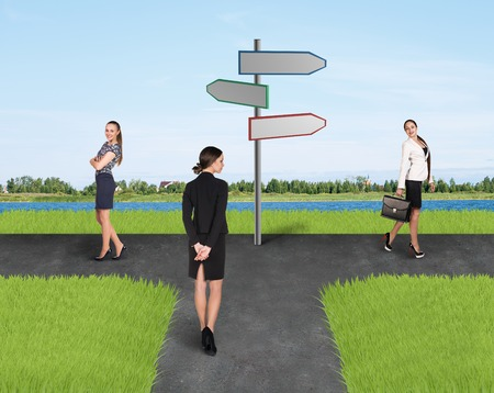 Two businesswomen standing at sign of right and left side and one of them back to camera photo