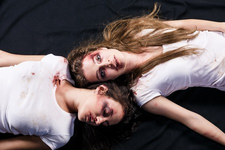 traumatised: Two young beaten women with cuts and bruises lie down on the floor on black background Stock Photo