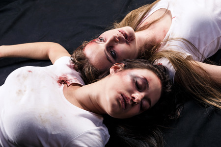 beaten: Two young beaten women with cuts and bruises lie down on the floor on black background Stock Photo