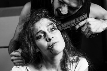 hostages: Crime. Beautiful girl kidnapped by criminals. Terrorist is threatening hostages with a gun.