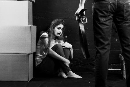 violencia intrafamiliar: Joven mujer es víctima de violencia doméstica y abuso emplazamiento en el suelo tiene miedo del hombre con cinturón negro sobre fondo blanco-y-