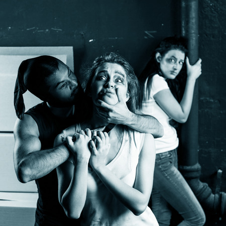 hostages: Crime. Two beautiful girls kidnapped by criminals. Terrorist is threatening hostages with a knife Stock Photo
