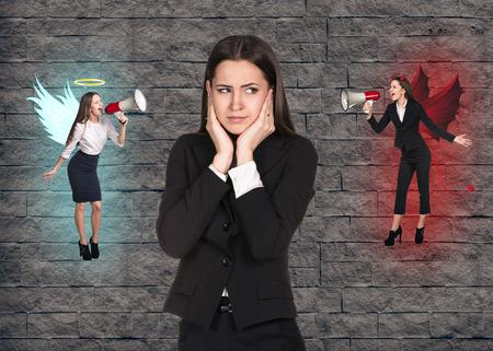 Junge unruhigen Geschäftsfrau, die Wahl zwischen Gut und Böse auf grauem Backstein-Hintergrund
