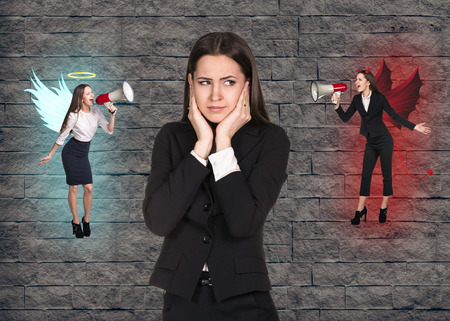 demon: Young troubled businesswoman making choice between good and bad on grey brick background