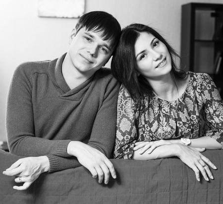 Couple leaning over their couch photo