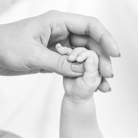 mum: hands of the baby and mom Stock Photo