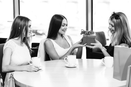 gifting: Cheerful young woman surprising friend with a gift in cafe