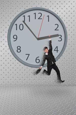 Man hang on clock on grey background photo