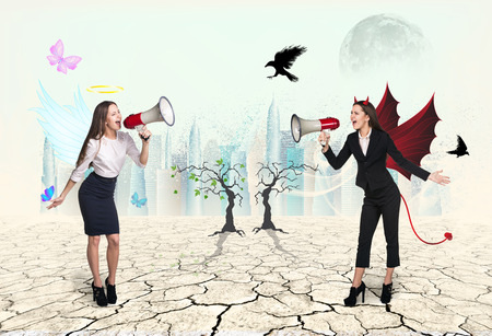 angel and devil: Portrait of angel and devil girls with megaphone in desert Stock Photo