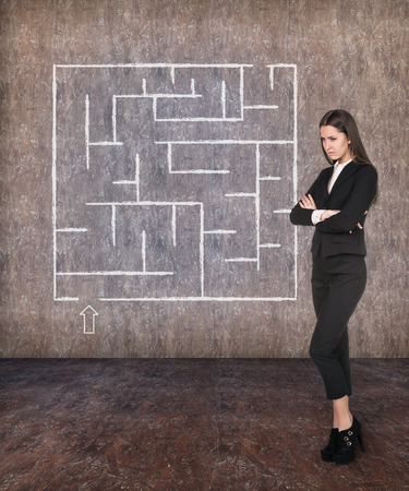 way of thinking: Young businesswoman looking at the labyrinth and thinking about right way on grey brick background Stock Photo